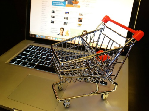 A tiny shopping cart atop the keyboard of a laptop computer