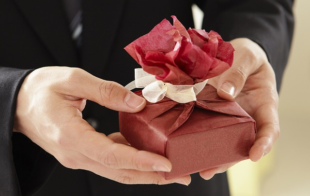 Person offering a small gift wrapped in red tissue paper