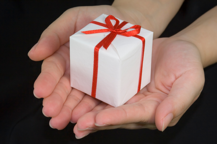 Small gift box wrapped in a bow and presented by a pair of hands