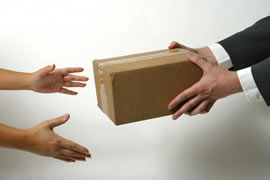 Man in suit jacket giving a parcel to a welcoming pair of hands