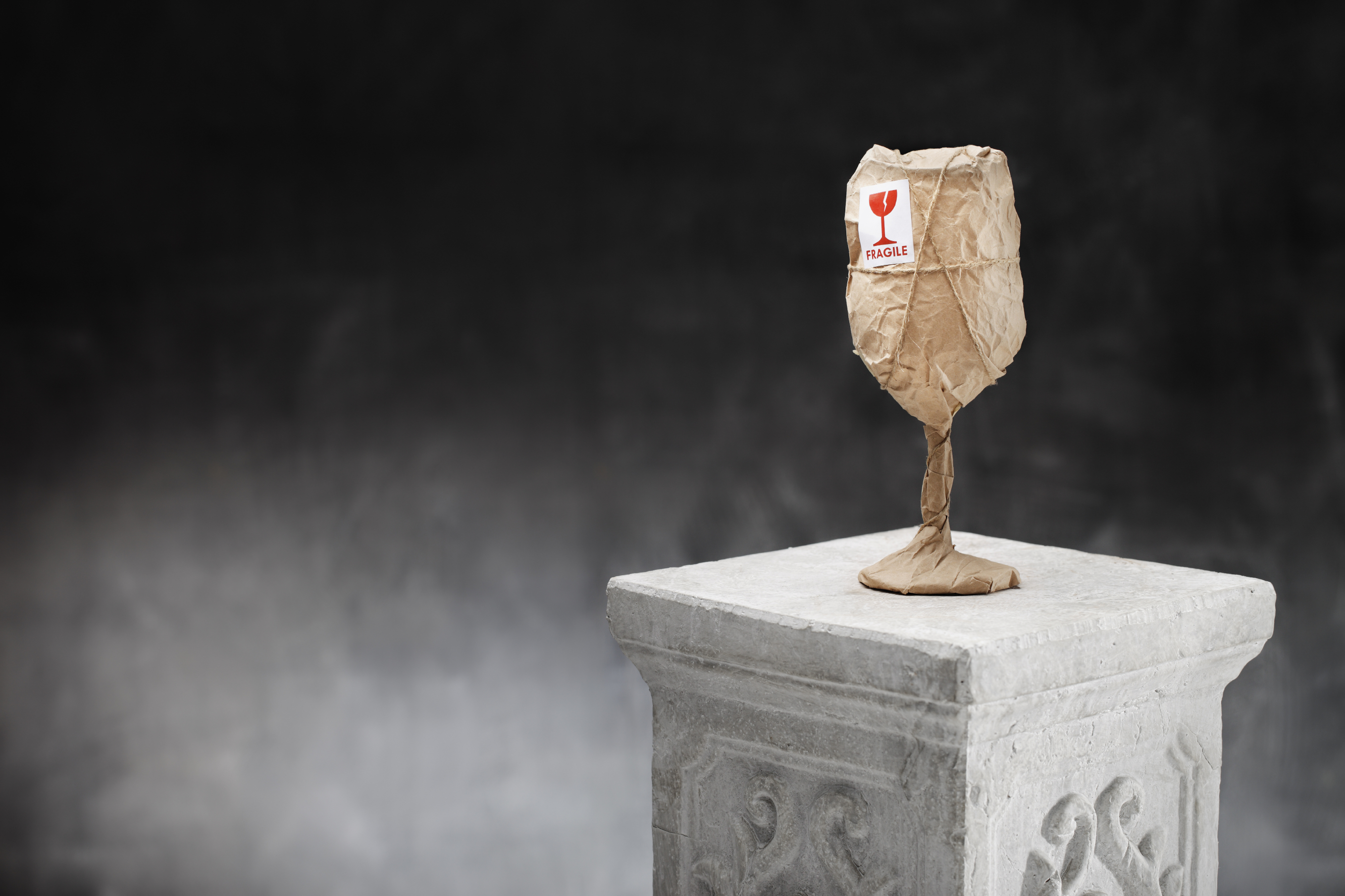 An obviously fragile wine glass wrapped in paper with a sticker marked FRAGILE