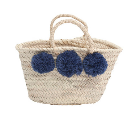 A French-inspired handwoven basket with pom poms