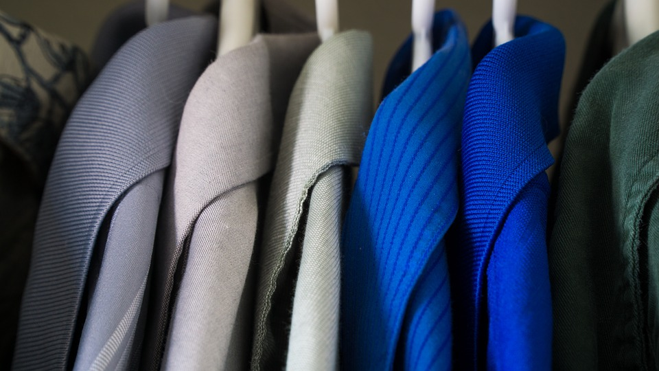 Clothing on hangers, mainly blazers, in a variety of sizes and colours