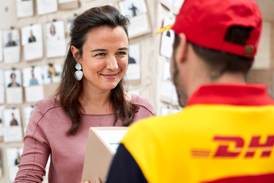 Woman smiling and receiving a parcel form a DHL Parcel UK delivery driver